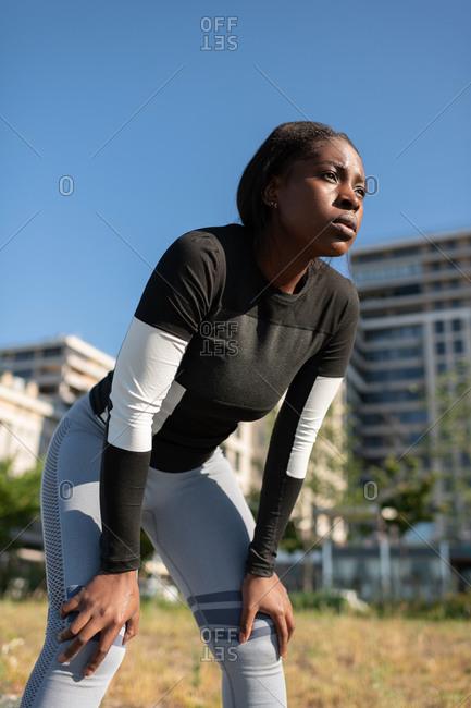 Tired african american runner resting on street