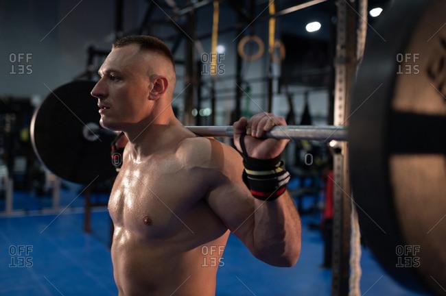 Powerful athlete doing back squat exercise