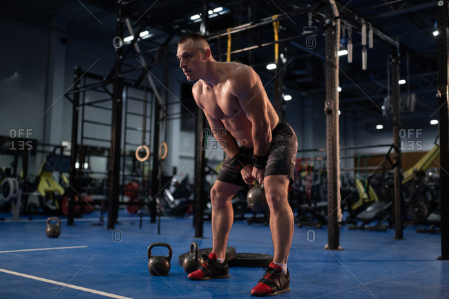 Muscular man exercising with kettlebell