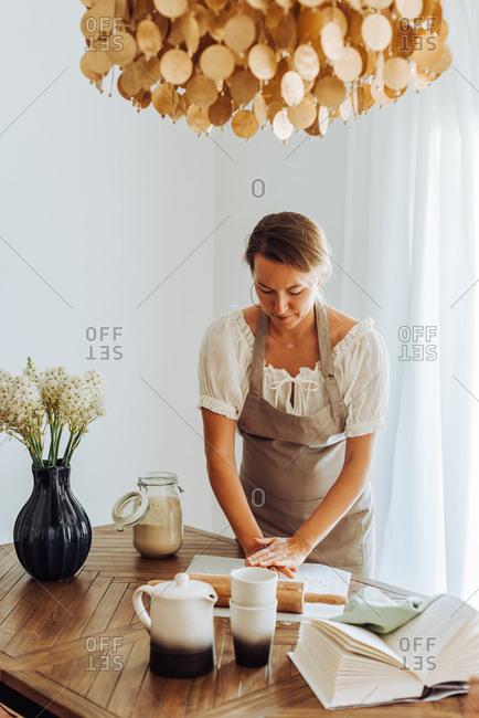 Housewife preparing dough standing at domestic kitchen, wearing apron
