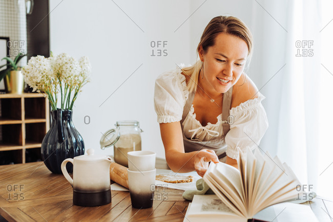 Woman reading book of recipes while cooking at kitchen table