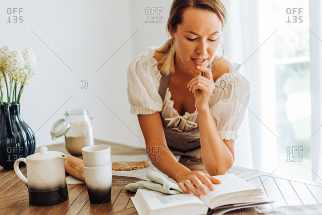 Woman reading a recipe book while cooking at kitchen