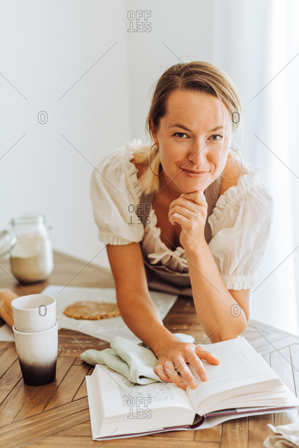 Woman with recipe book looking at camera while cooking at kitchen and