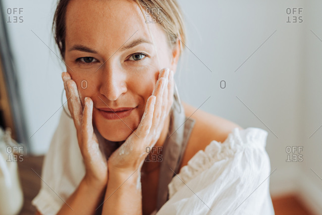 Close up of woman with flour on hands in kitchen, looking at camera