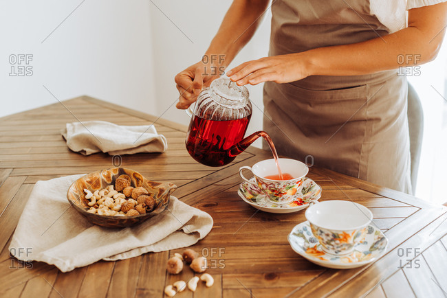 Midsection of woman pouring hibiscus tea in cups on table