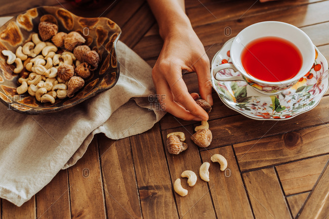 Cup of hibiscus tea, hand and dry fruits on top of a table