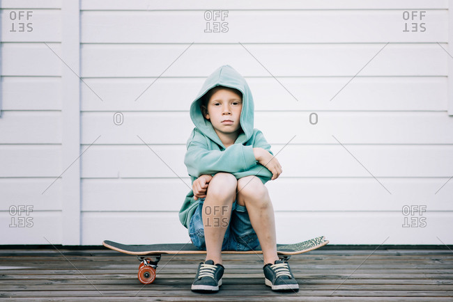 Young boy sat on a skateboard with a hoodie on looking grumpy