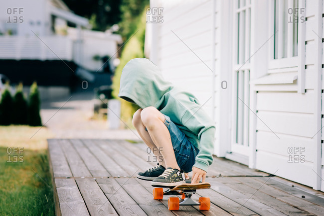 Boy sat on a skateboard with his hood up hiding his face