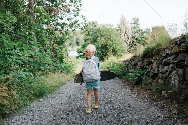 Young girl walking down a country lane with a skateboard and backpack