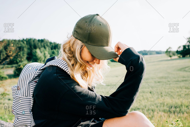 Woman sat in the countryside holding her cap over her face looking shy