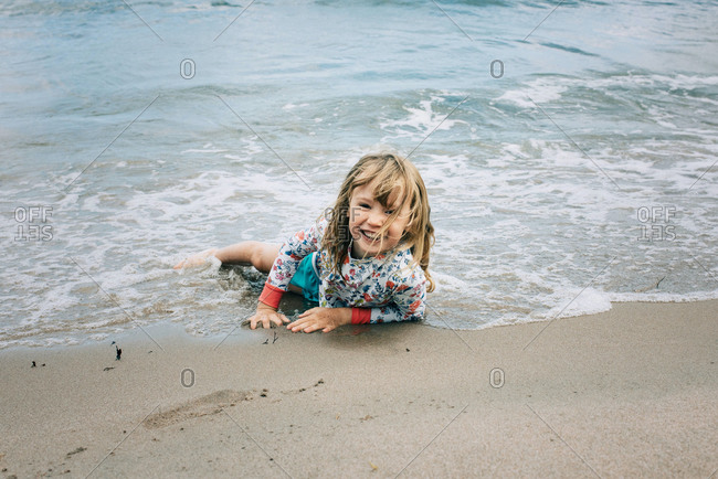 Young girl laying in the water at the beach smiling