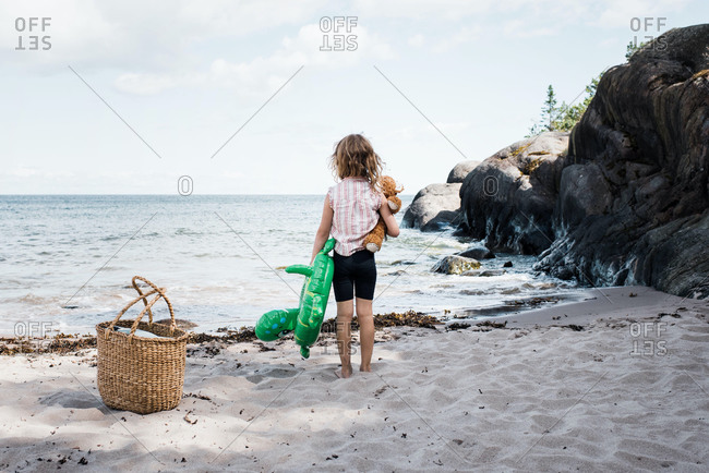 Girl stood on the beach holding her bear and inflatable by the sea