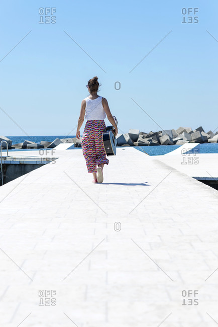 Young woman with ponytail walking along promenade with a guitar