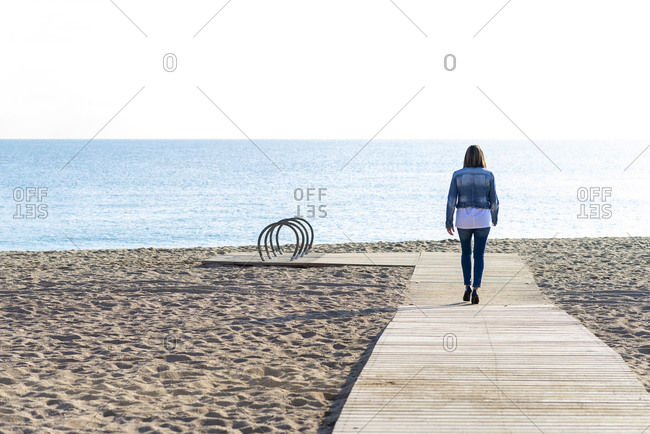 Rear view of a woman walking on footpath to seashore in sunny day