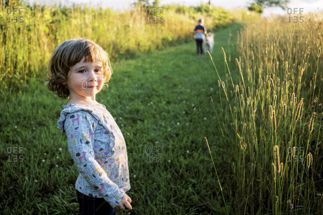 Little girl with a smeared and messy mouth standing in a field happily