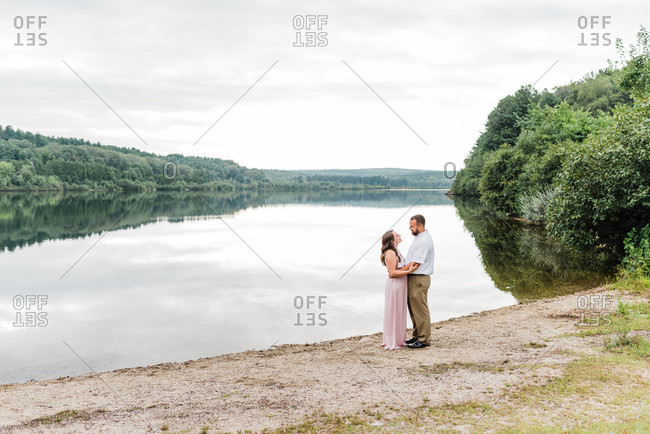 A couple looking at each other by a lake