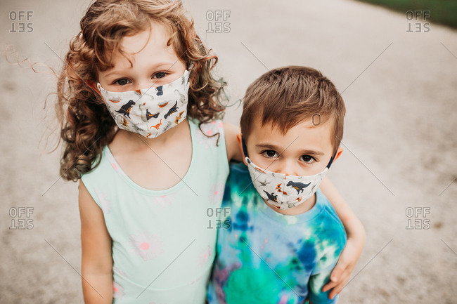 Close up of two young kids outside wearing homemade masks