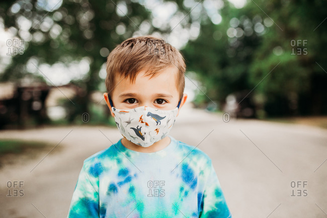 Preschool age boy standing outside wearing homemade fabric mask