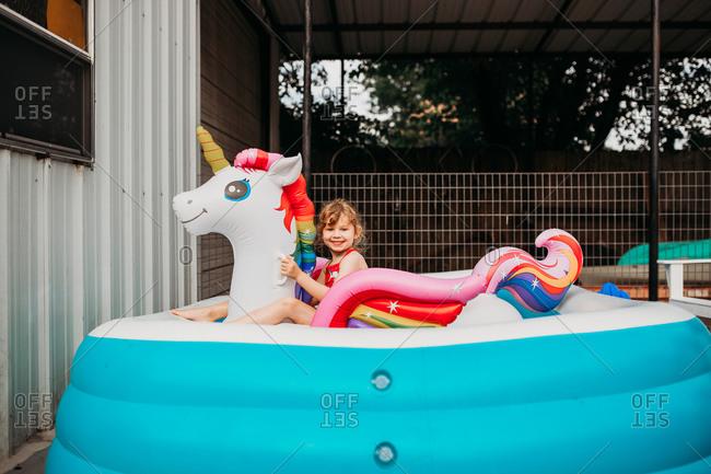 Young girl sitting on inflatible rainbow unicorn in back yard pool
