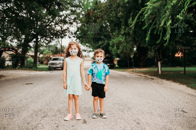 Two young kids standing outside wearing homemade fabric masks