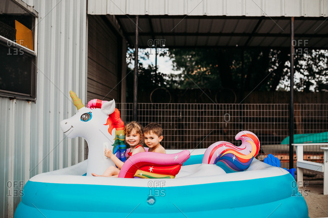 Two young kids sitting on inflatible unicorn in back yard pool