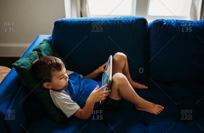 Over head view of young boy laying on couch with tablet