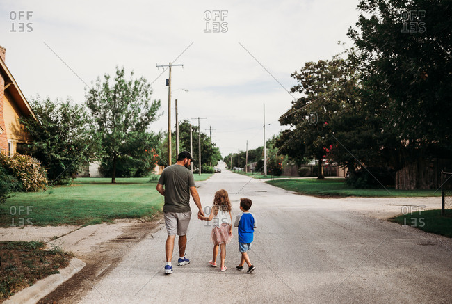 Dad and two young kids going on a walk in neighborhood