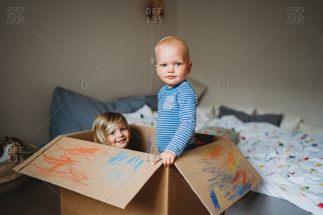 Brothers playing and drawing in a box during lockdown