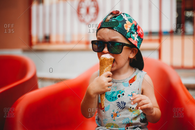 Young toddler eating ice cream cone with cap to back and sunglasses