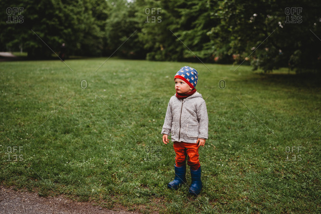 Young boy with serious face standing at the park looking to the side
