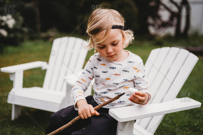 Boy with dirty mouth putting marshmallow on stick to make smores