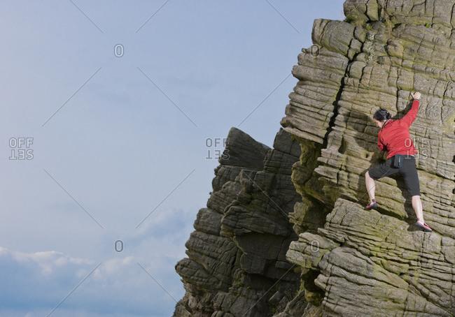 Woman climbing at wind gather rocks in the british peak district
