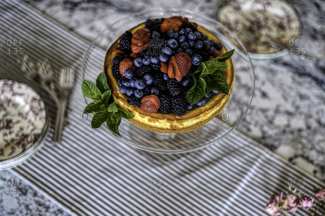 Cheesecake and berries with mint leaves