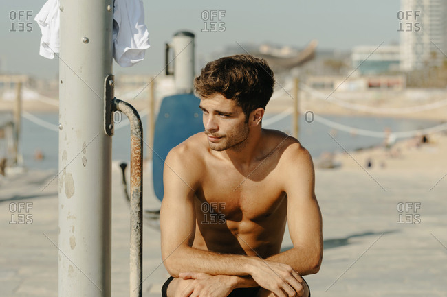 Young handsome men portrait exercising at the beach