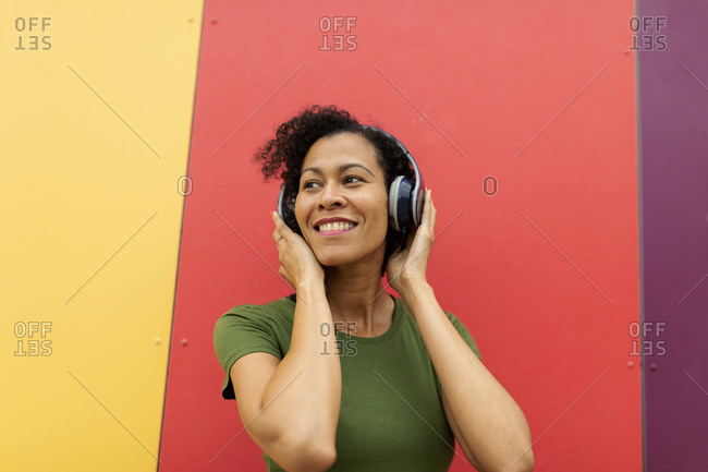 Latin woman wearing headphone listen to music against colorful wall