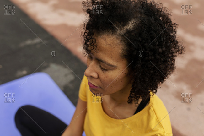 Peaceful latin woman sitting on floor practicing yoga