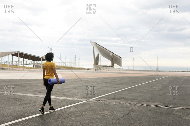Curly hair woman walking outdoors with yoga mat