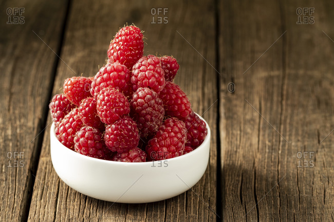 Fresh ripe raspberries in a white ceramic bowl on a dark brown wooden table with space for text