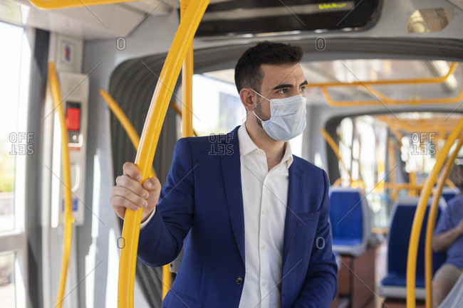 Young man in suit and mask using public transport