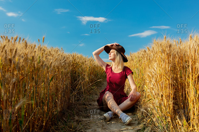 Blonde girl in hat and red dress is sitting on ground in a wheat