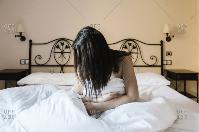 Woman hiding behind her hair in bed