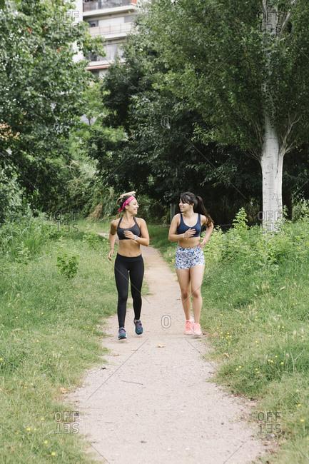 Two women jogging on rural sidewalk