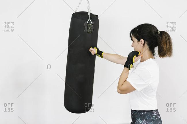 Mature woman training boxing at gym