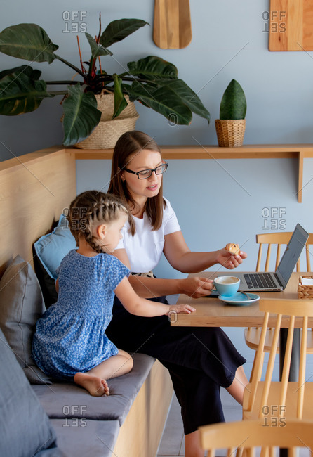 Mother with her daughter trying to work in a cafe