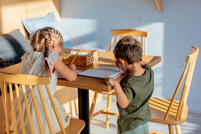 Little boy and girl drawing pictures while sitting at a table in a cafe