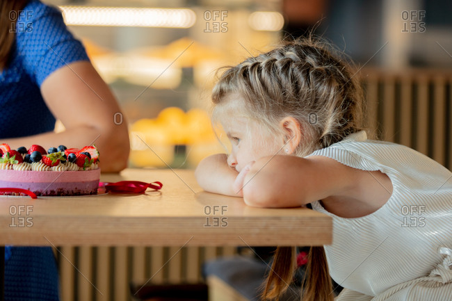 Little sad girl staring at a glute-free cake in cafe
