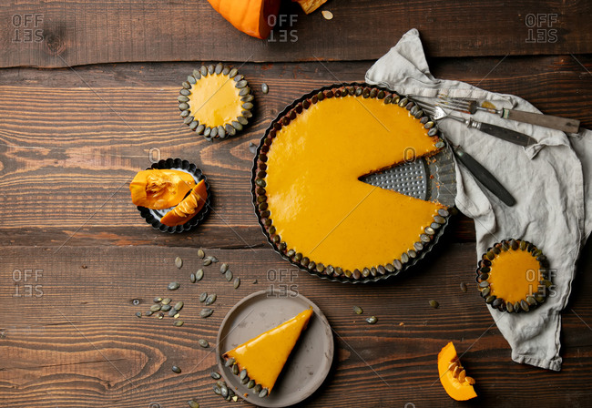 Overhead view of fresh pumpkin pie with cold cream inside on a wooden table