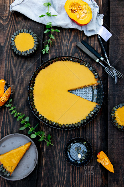 Fresh pumpkin pie with cold cream inside on a wooden table viewed from above