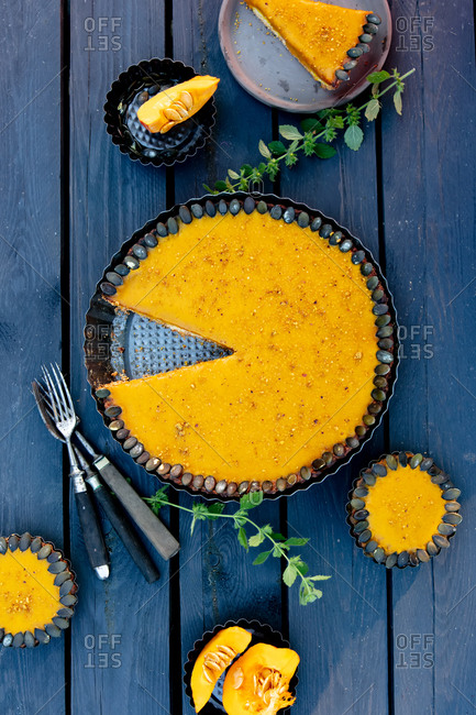 Fresh pumpkin pie with cold cream inside on a wooden table missing a slice