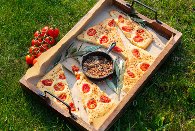 Traditional Italian focaccia bread and pan with salt on a tray outdoors